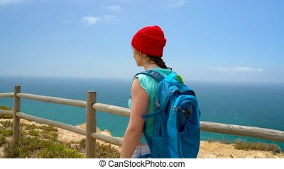 Woman with a backpack goes on a picturesque hilly terrain to...