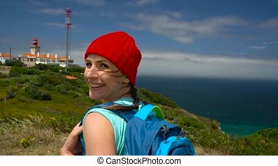 Woman with a backpack goes on a picturesque hilly terrain to the ocean