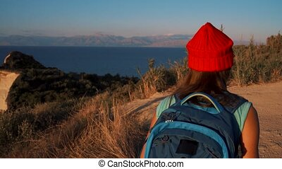 Woman with a backpack goes to the Cape Drastis at Corfu island in Greece