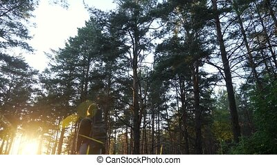 woman with a backpack goes towards sunset.