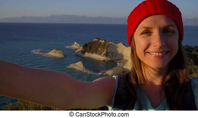 Woman with a backpack makes selfie on the background of the Cape Drastis at Corfu island in Greece