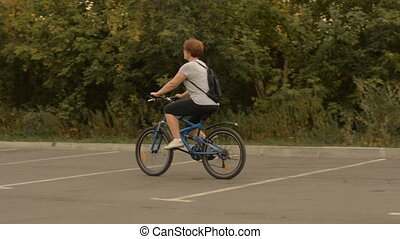 Woman with a backpack riding a bicycle in a parking lot for...