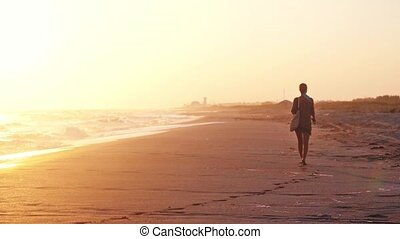 Woman with a bag and beach shoes in hands walking on beach...