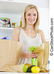 woman with a bag of groceries shopping in the kitchen