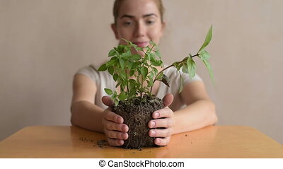 Woman with a basil sprout. She is holding the sprout in her...