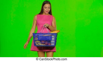 Woman with a basket enjoying the scent of pepper. Green screen