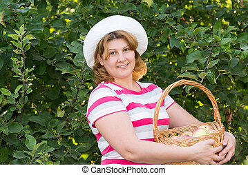 Woman with a basket of apples in garden
