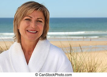 Woman with a bathrobe on the beach