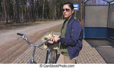 Woman with a bicycle waiting for bus