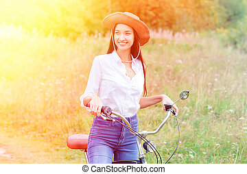 Woman with a black bicycle in a summer park or forest