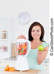 Woman with a blender and an apple
