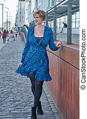 woman with a blue dress on the street smiling
