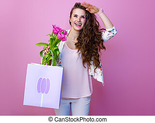 woman with a bouquet of flowers and shopping bag looking into the distance