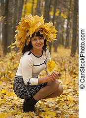 Woman with a bouquet of maple leaves sitting on the grass in the autumn park.
