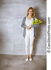 Woman with a bouquet of yellow tulips standing by the wall