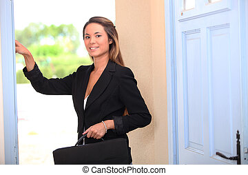 Woman with a briefcase ringing a front door bell