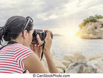 Woman with a camera photographing the sunset on the sea coast.