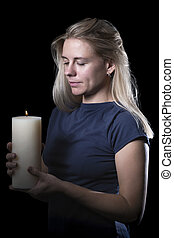 Woman with a candle in the dark