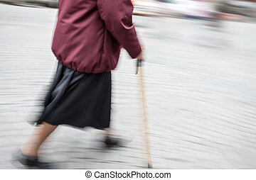 woman with a cane walking down the street
