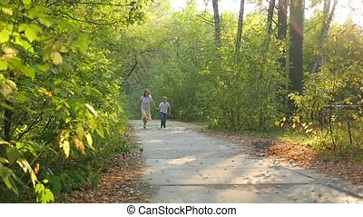 woman with a child running along a path in a park holding hands