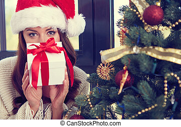 Woman with a Christmas Gift next to christmastree
