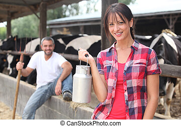 Woman with a churn of milk in front of a herd of cows