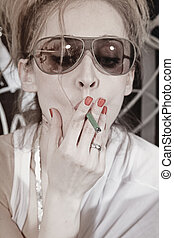 Woman with a cigarette wearing sunglasses