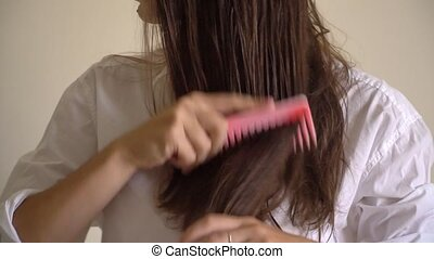 Woman with a comb in her hand brushing wet hair after bath