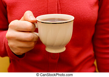 Woman with a cup of black tea in her hand