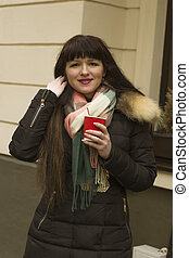 Woman with a cup of coffee at the street in winter