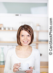 Woman with a cup of coffee in the kitchen