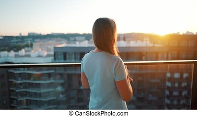 Woman with a cup of coffee or tea goes to the balcony to admire the sunset