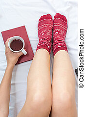 Woman with a cup of tea in bed