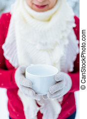 Woman with a cup of tea in the winter outdoors