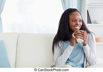 Woman with a cup on couch