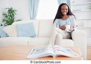 Woman with a cup on the sofa - Smiling woman with a cup on ...