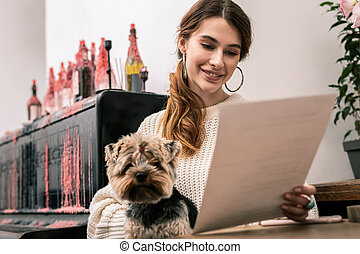 Woman with a dog in her hands reading the menu