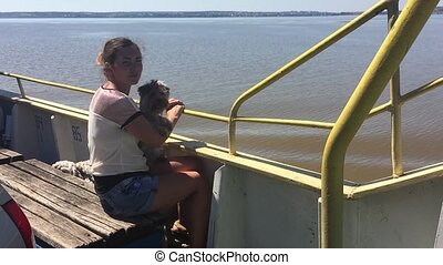 woman with a dog on a ship sailing on the river slow motion video. girl with a pet on the deck of a ship floating on the water