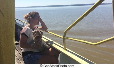 woman with a dog on a ship sailing on the river slow motion video. girl with a pet on the deck of a ship floating on the water slow motion video
