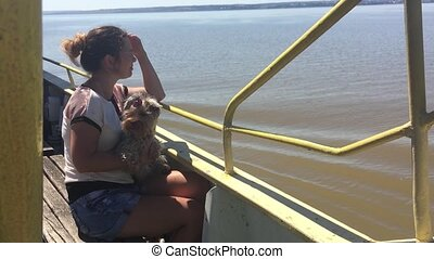 woman with a dog on a ship sailing on the river slow motion video. girl with pet on the deck of a ship floating on the water slow motion video