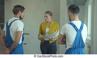 Woman with a drawing talks to repairmen