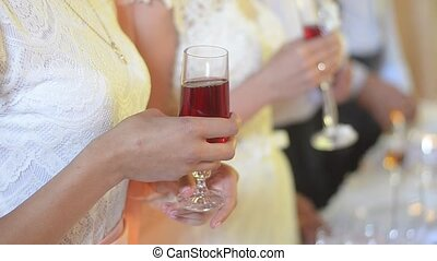 Woman with a glass in her hands applauding. Hands of the guest at the wedding. Camera flashes. Toast. Wedding reception.