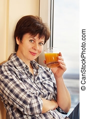 Woman with a glass of juice sitting near the window