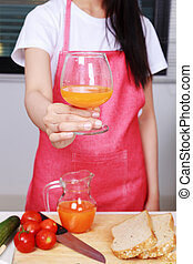 woman with a glass of orange juice in kitchen room