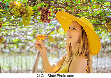 Woman with a glass of wine in the vineyard