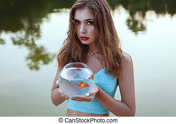 Woman with a goldfish. - Woman is holding an aquarium with a...