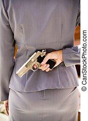 Woman with a gun - Woman hiding a gun behind her back