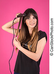 Woman with a hair curler. Girl with disheveled hair on a pink background.