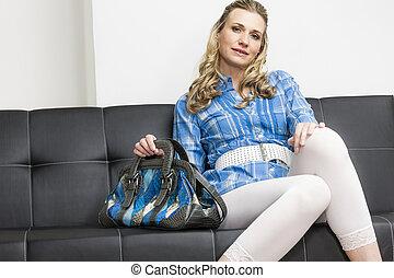 woman with a handbag sitting on sofa