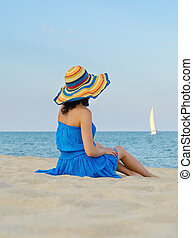 Woman with a hat on sandy beach